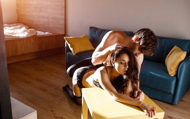 Young sexy couple in living room. dominant man stand on knees upon woman in lingerie and hold her hair in hands. sensual moment. lust and bdsm. together in room