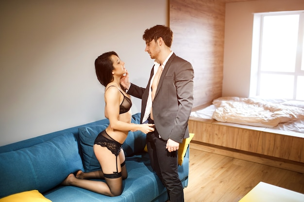 Young sexy couple in living room. man in suit touching face of prostitute and look at her. young woman in black lingerie stand on knees on sofa. bdsm and lust.