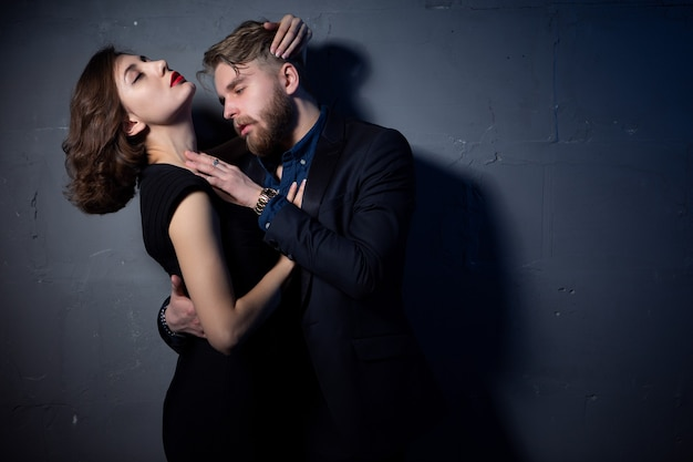 A young sexy couple passionately embraces in a room with low lighting. close-up portrait.