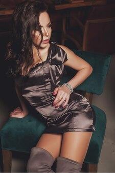 Молодая сексуальная милая стильная женщина в красивом блестящем сером платье на темном внутреннем фоне ресторана. довольно женщина позирует для фото рекламного бизнеса. концепция рекламного фото. копировать пространство