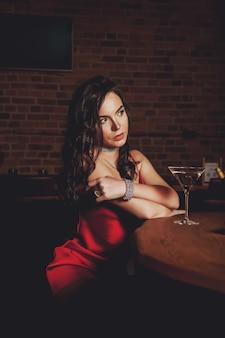 Молодая сексуальная милая стильная женщина в красивом блестящем красном платье на темном фоне интерьера ресторана