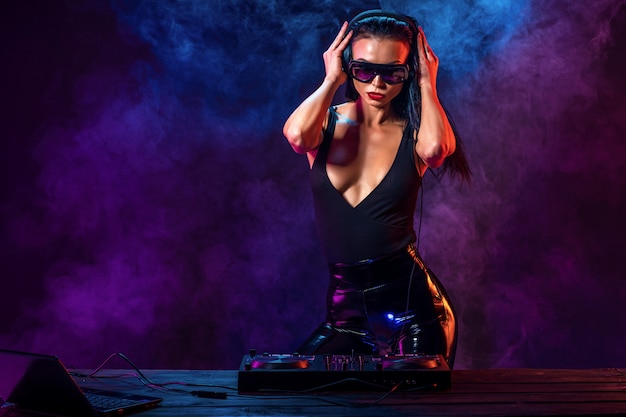 Young sexy dj with sunglasses playing music