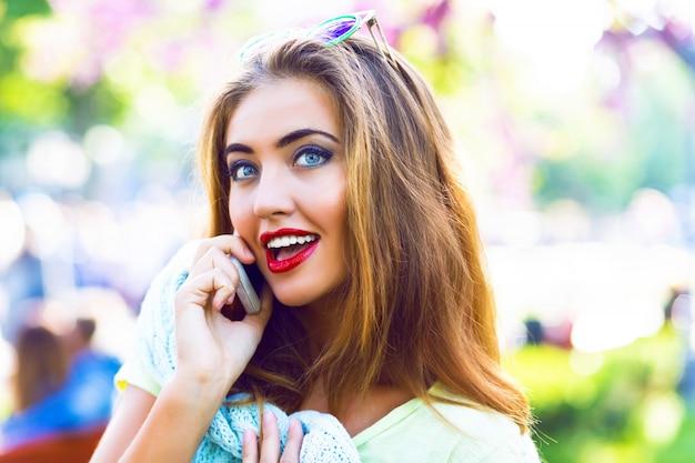 若いセクシーなエレガントな女性が通りでポーズし、友人、パステル調のカジュアルな服、日当たりの良い色、春、屋外、ロマンチックな場所で彼女のスマートフォンで話します。