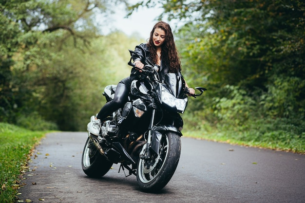 Young sexy girl in a black leather jacket sitting on a black sports motorcycle on a forest road
