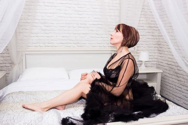 Young sexy girl in a black peignoir sits on a white bed