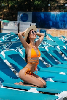 A young sexy girl in glasses and a hat is smiling happily and sunbathing on a sun lounger on a sunny day. happy vacation vacation. summer holidays and tourism.