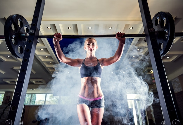 Young sexy girl in the gym preparing to do squat on smoke background