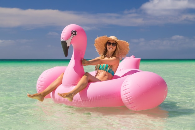 Young and sexy girl having fun and laughing on an inflatable giant pink flamingo float mattress in a bikini on the sea. attractive tanned woman lies in the sun on vacation