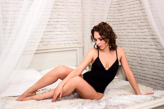 검은 peignoir에 젊은 섹시 한 여자는 흰색 침대에 앉아