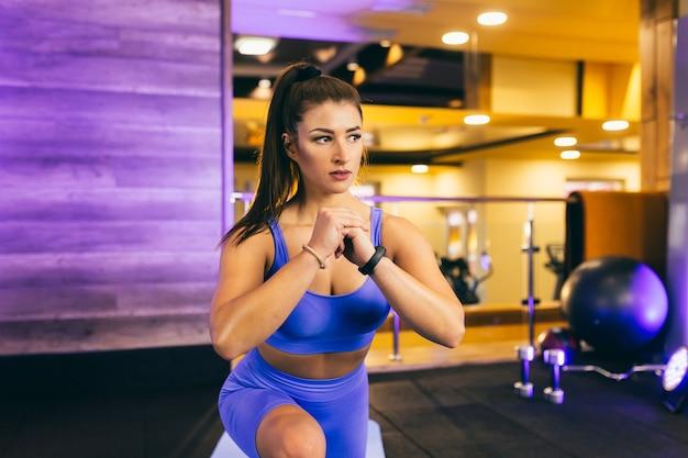 Молодая сексуальная девушка выполняет разминку в тренажерном зале и позирует в синей одежде