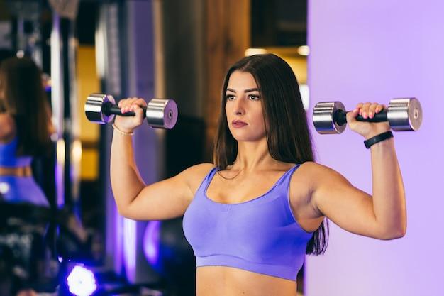 若いセクシーな女の子は、ジムでダンベルを使ってスポーツ運動を行います。青い服を着て