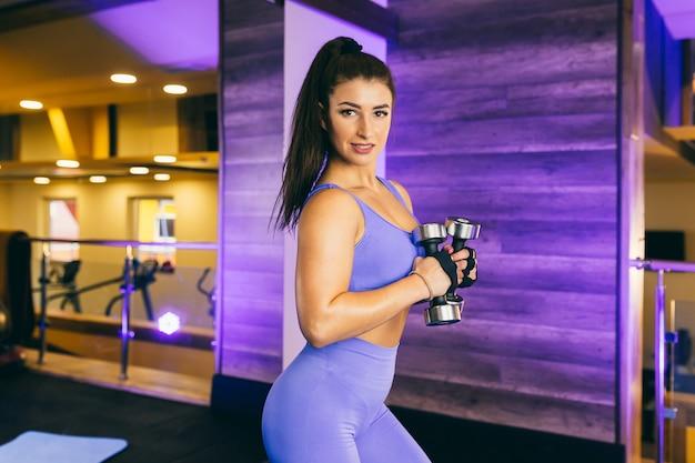 섹시 한 젊은 여자는 체육관에서 아령으로 스포츠 연습을 수행합니다. 파란색 옷을 입고