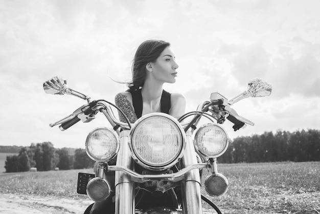 Молодая сексуальная девушка позирует на мотоцикле на закате. концепция автоспорта. смешанная техника