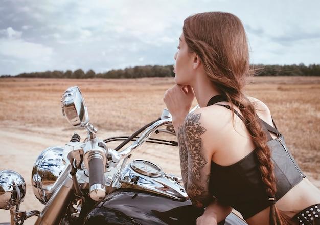 일몰에 오토바이에 포즈 젊은 섹시 한 소녀. 모터 스포츠 개념입니다. 혼합 매체