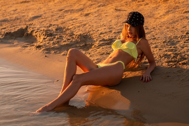 Young sexy girl at sunset at the beach