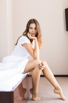 Young sexy girl in underwear sitting on bed in the morning