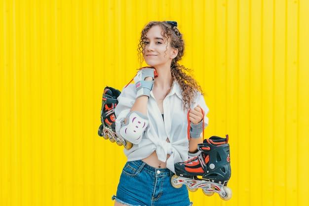 Молодая сексуальная счастливая девушка держит ролики на желтой стене