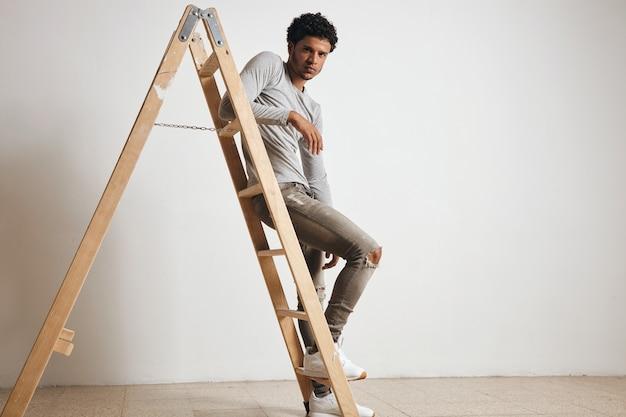 若いセクシーなラテン男は空白の灰色のヘンリー長袖を着て、ジーンズは白で隔離された木製のはしごに座っています