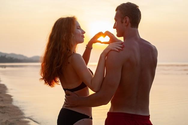 Молодая сексуальная романтическая влюбленная пара счастлива на летнем пляже, вместе веселясь в купальных костюмах, показывая знак сердца на сандет