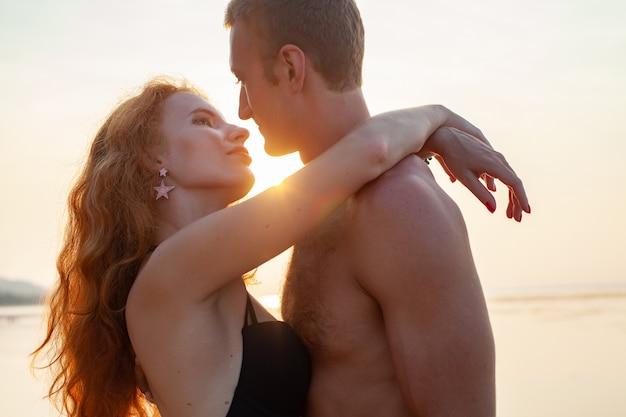 Молодая сексуальная романтическая влюбленная пара счастлива на летнем пляже, вместе веселясь в купальных костюмах
