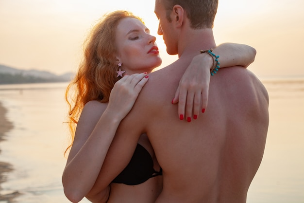 一緒に水着を着て楽しんで夏のビーチで幸せな恋に若いセクシーなロマンチックなカップル