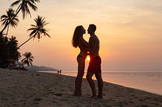 Молодая сексуальная романтическая пара в любви на закате счастлива на летнем пляже вместе весело в купальных костюмах
