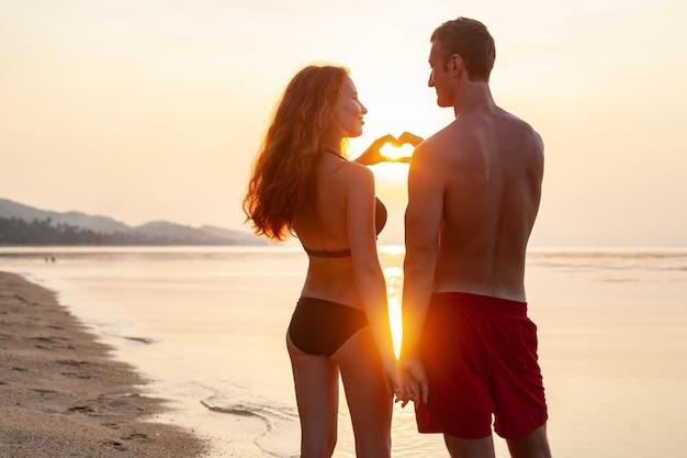 Giovane coppia romantica sexy innamorata felice sulla spiaggia d'estate insieme divertendosi indossando costumi da bagno mostrando il segno del cuore sul sundet