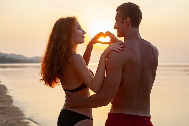 Young sexy romantic couple in love happy on summer beach together having fun wearing swim suits showing heart sign on sundet
