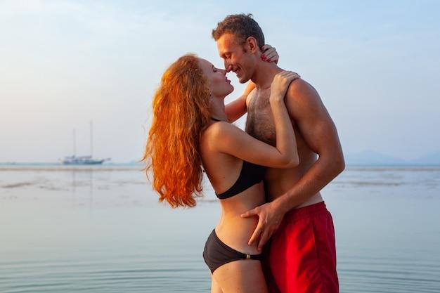 Giovane coppia romantica sexy innamorata felice sulla spiaggia estiva insieme divertendosi indossando costumi da bagno