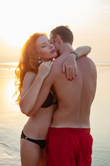 Young sexy romantic couple in love happy on summer beach together having fun wearing swim suits