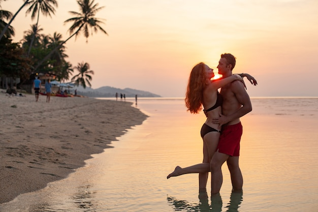 Young sexy romantic couple in love on sunset happy on summer beach together having fun wearing swim suits
