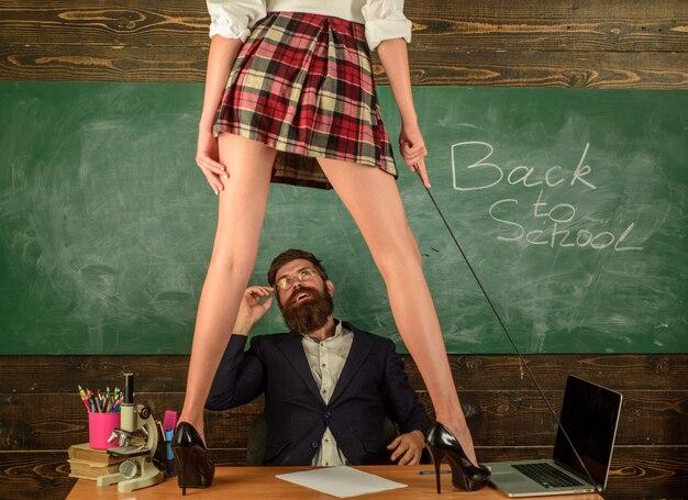 Молодая сексуальная школьница, студентка и учитель. сексуальная студентка школьница с соблазнением короткой школьной юбки удивила учителя в классе. девушка-студент нарушает правила школьной одежды. дресс-код.