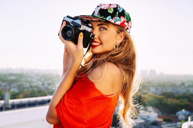 Молодая сексуальная чувственная белокурая женщина, делающая фото на ретро старинную хипстерскую камеру, улыбаясь и весело, в яркой шляпе с цветочным орнаментом.