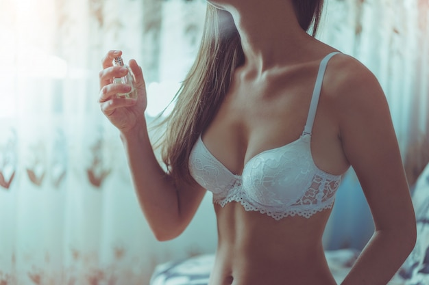 Young sexy sensual seductive woman having beautiful body and soft skin with bottle of womens perfume at home. female wearing white lace lingerie.
