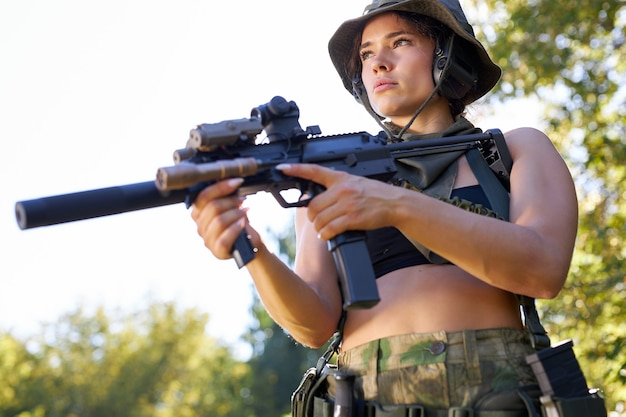 Young sexy slender caucasian woman soldier shooting with rifle machine gun in the wild forest