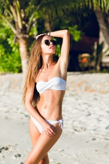Young sexy slim girl standing on a beach wearing white bikini swimwear. she wears dark sunglasses and has long dark hair she is tanned and stylish.