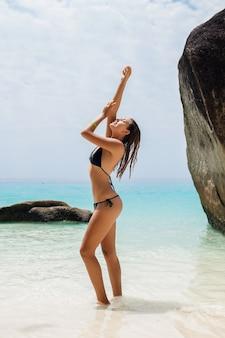 Giovane donna sottile sexy, bel corpo perfetto, pelle abbronzata, costume da bagno bikini nero, prendere il sole nell'oceano di acque cristalline, vacanze estive in asia, sensuale, caldo, viaggio in thailandia, spiaggia tropicale