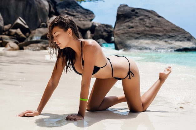Young sexy slim woman, beautiful perfect body, tanned skin, black bikini swimsuit, sunbathing, ocean, summer vacation in asia, sensual, hot, travel in thailand, tropical beach, similan islands