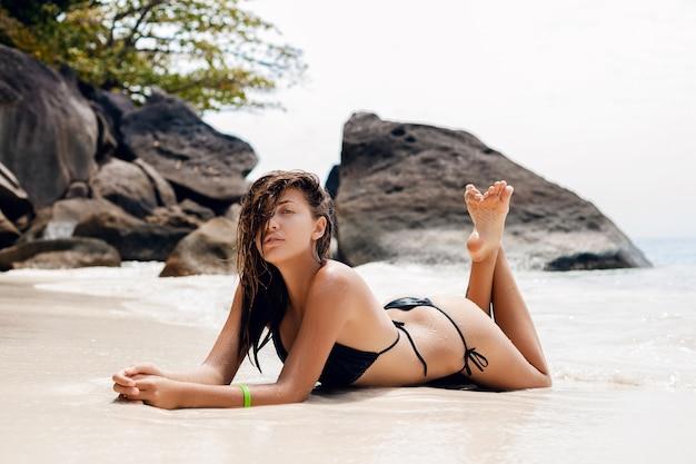 Молодая сексуальная стройная женщина, красивое идеальное тело, загорелая кожа, черный купальник бикини, солнечные ванны, океан, летние каникулы в азии, чувственное, жаркое, путешествие по тайланду, тропический пляж, симиланские острова