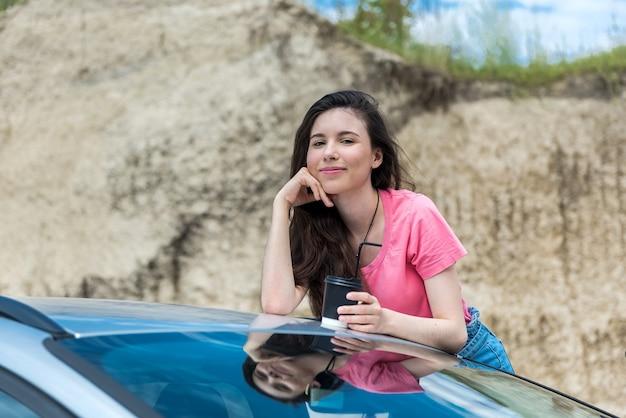 여름 방학 동안 도로에 그녀의 차에서 포즈 젊은 섹시 슬림 여자