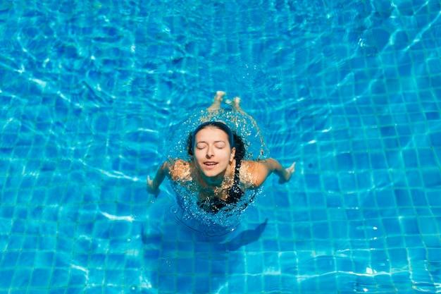 Молодая сексуальная стройная женщина расслабляющий в бассейне с кристально голубой водой