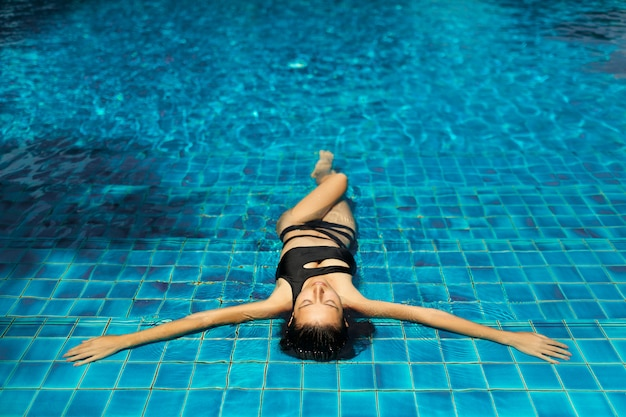 Young sexy slim woman relaxing in tropical swimming pool with crystal blue water in hot summer day