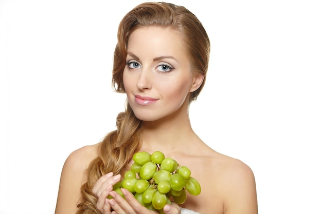 Young sexy smiling beautiful woman holding a bunch of grape in her hands with long hair isolated on white