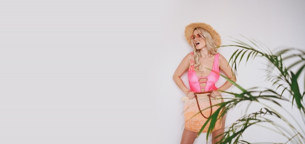 Young sexy smiling happy blonde in a pink swimsuit, a straw hat, sunglasses, excited to present product. woman on a white background with palm green leaves.
