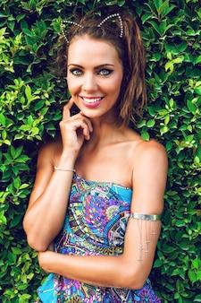 Молодая сексуальная улыбающаяся счастливая женщина позирует в саду в прекрасный солнечный день, носит яркое стильное платье, наслаждается отпуском и весело.