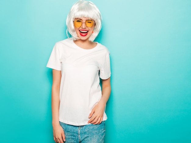 白いかつらと赤い唇の若いセクシーな笑みを浮かべて内気な少女。夏の服の美しいトレンディな女性。丸いサングラスに夢中になるスタジオ夏の青い壁に近いポーズの屈託のないモデル