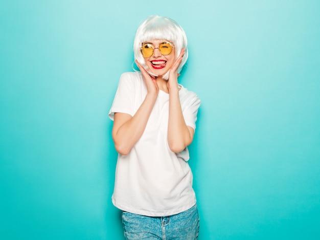 白いかつらと赤い唇の若いセクシーな笑みを浮かべて内気な少女。夏服で美しいトレンディな女性。クレイジーになるスタジオ夏の青い壁に近いポーズの屈託のないモデル