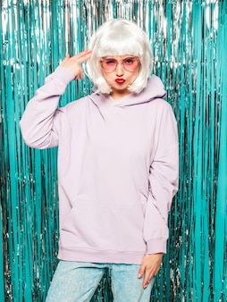 Young sexy smiling hipster girl in white wig and red lips.beautiful trendy woman in summer clothes.upset model posing on blue silver shiny tinsel background in studio.female immitating gun
