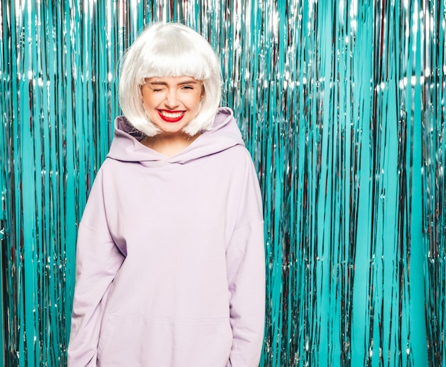 Young sexy smiling hipster girl in white wig and red lips.beautiful trendy woman in summer clothes.upset model posing on blue silver shiny tinsel background in studio going crazy