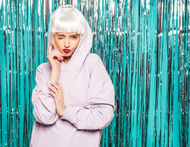 Young sexy smiling hipster girl in white wig and red lips.beautiful woman in summer clothes. makes duck face